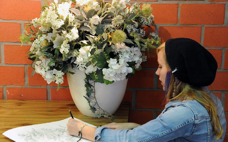 Bahrain's Katie Allen uses a vase full of artificial flowers as a subject in the drawing workshop at Creative Connections.