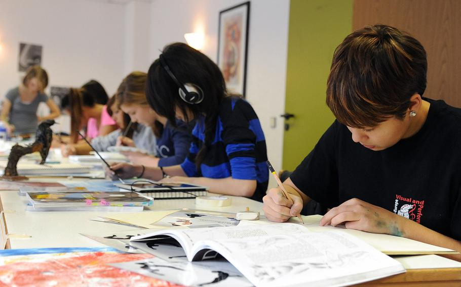 Shayna Petersen of Hohenfels and other members of the mixed media workshop at Creative Connections concentrate on their art works.