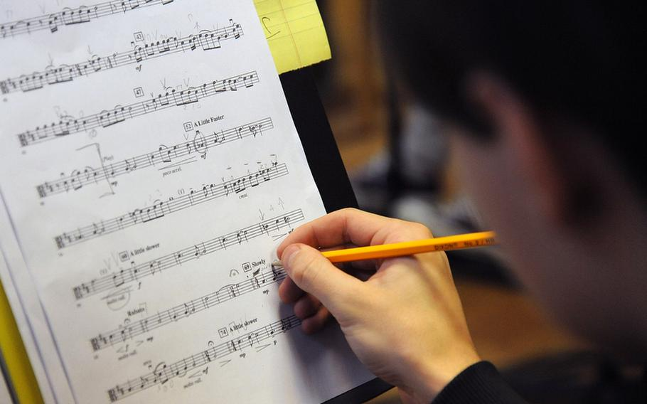 Joseph Spiszer of Wiesbaden makes a note on his sheet music as the strings workshop rehearses a piece at the this year's Creative Connections program for DODDS-Europe high school seniors.
