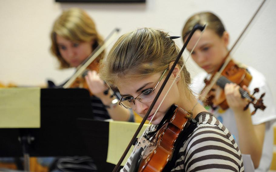 Grace Babinski of Ankara follows the notes as the strings workshop rehearses a piece at this year's Creative Connections workshop for DODDS-Europe high school students.