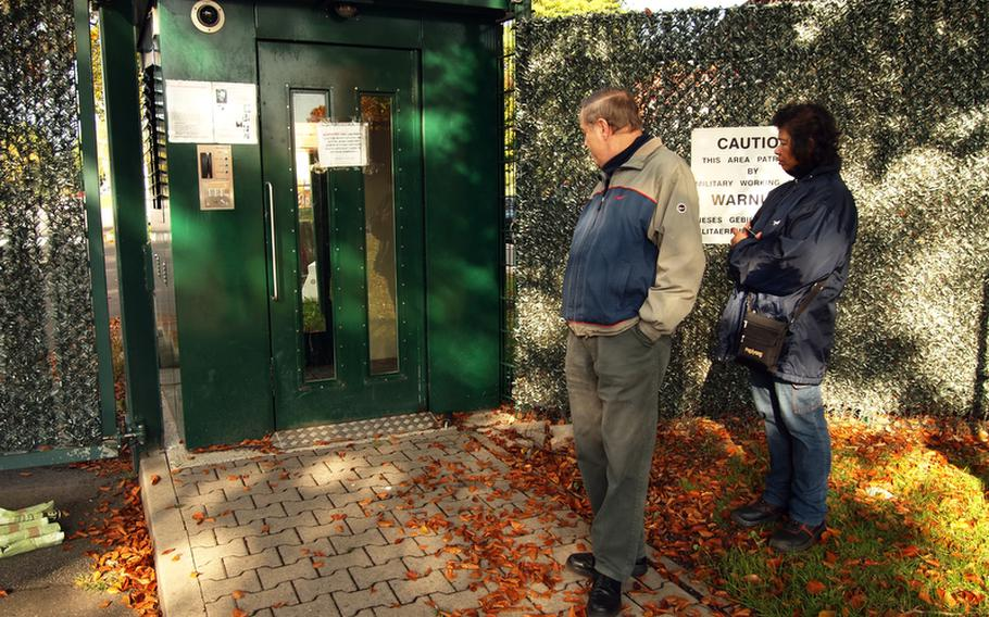 Guenther Laier and his wife Lamom wait outside Kleber Kaserne in Kaiserslautern for someone to reset an automated pedestrian gate on the fritz. After scanning her ID and getting into the gate's double-doored booth, an automated voice told Lamom, who works as a cleaner on base, to exit. Then the gate froze up.