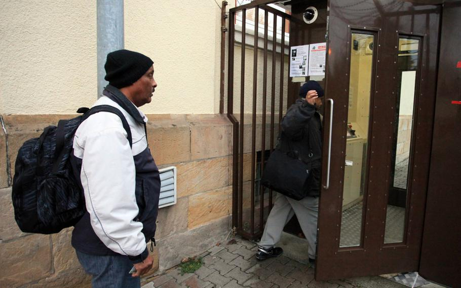 A worker waits for a colleague to enter Kleber Kaserne, a U.S. Army base in Kaiserslautern, through an automated pedestrian gate. The first man got through fine; after having trouble with the fingerprint scanner, the second man pressed a button to call a guard who buzzed him in.