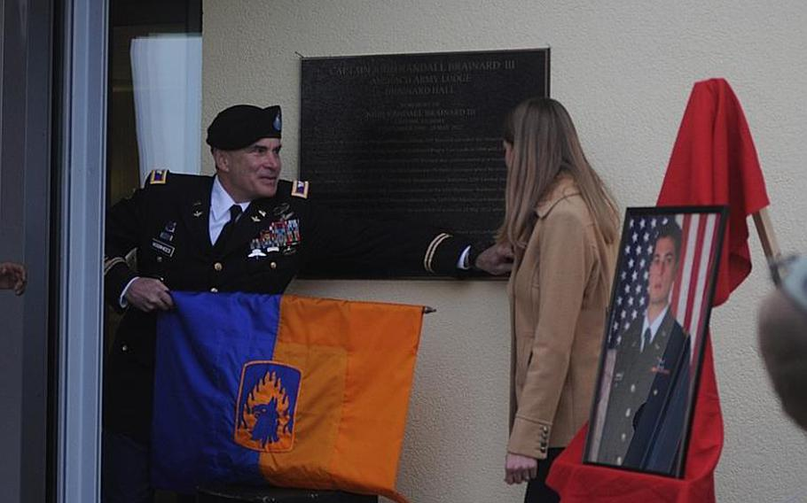 """Col. Jay Voorhees, commander of the 12th Combat Aviation Brigade, and Emily Brainard unveil a marker describing the life and career of her husband, Capt. John """"Jay"""" Brainard, on Friday, Nov. 9, 2012, on Urlas Kaserne in Ansbach, Germany. Capt. ''Jay'' Brainard was killed in Afghanistan in May. The ceremony Friday dedicated the Army lodging facility on Urlas Kaserne in his memory."""