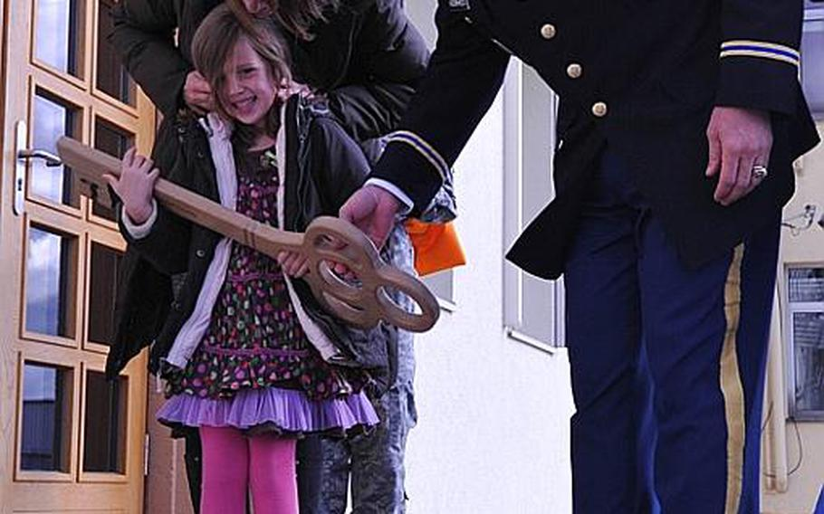 Emma Pratt, daughter of Chief Warrant Officer 5 John C. Pratt, holds the ceremonial key to the newly named Pratt Headquarters building on Katterbach Kaserne in Germany. The 12th Combat Aviation Brigade's headquarters was renamed on Nov. 2  in honor of Emma's father, who died in May in Afghanistan. Also pictured is Pratt's wife, Nicola, and the 12th CAB commander, Col. Jay Voorhees.