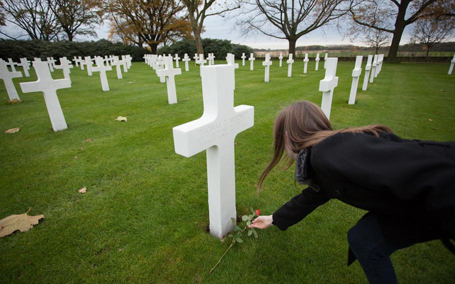 Samantha, a British sixth-grader at AFNORTH International School, places a rose on the grave of 2nd Lt. Thomas C. Mooney, a Pennsylvanian who died Feb. 10, 1944. Students visited the Netherlands American Cemetery and Monument on Friday, Nov. 9, 2012, for a Veterans Day ceremony.