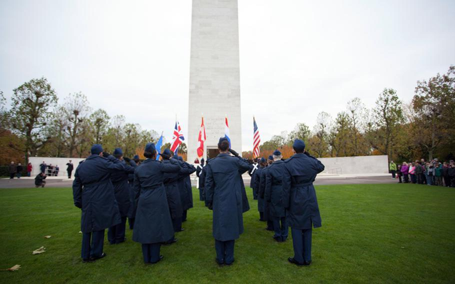 Members of an ROTC honor guard from AFNORTH International School salute while sixth-graders from the school look on during a Veterans Day ceremony Friday, Nov. 9, 2012, at Netherlands American Cemetery and Monument in Margraten, Netherlands.