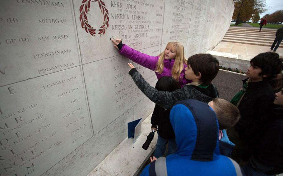 Sixth-graders from AFNORTH International School point at a rosette that indicates an American servicemember previously listed as missing has been found. There is a hole next to the name of Pfc. Gerald Kight, whose remains were found last year in a World War II foxhole. A rosette was placed next to his name in a ceremony Friday, Nov. 9, 2012.