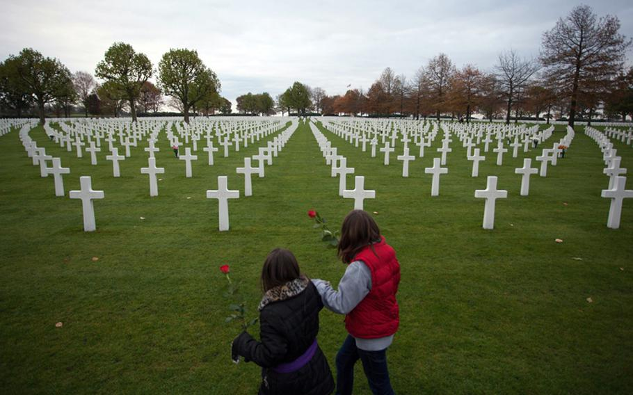 Sixth-graders from AFNORTH International School carry roses on Friday, Nov. 9, 2012, to place on the graves of servicemembers they researched as part of a Veterans Day remembrance at the Netherlands American Cemetery and Monument.
