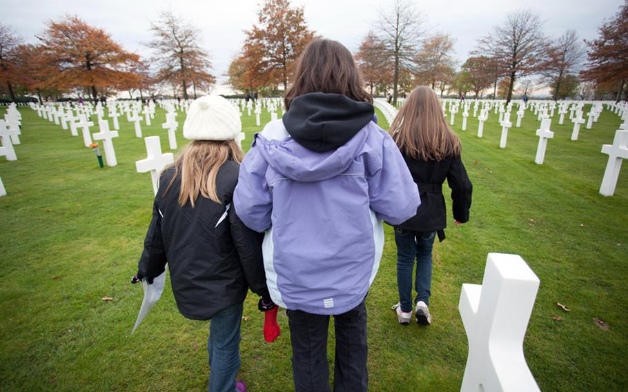 Sixth-graders from AFNORTH International School look for graves on which to place roses at the Netherlands American Cemetery and Monument on Friday, Nov. 9, 2012.