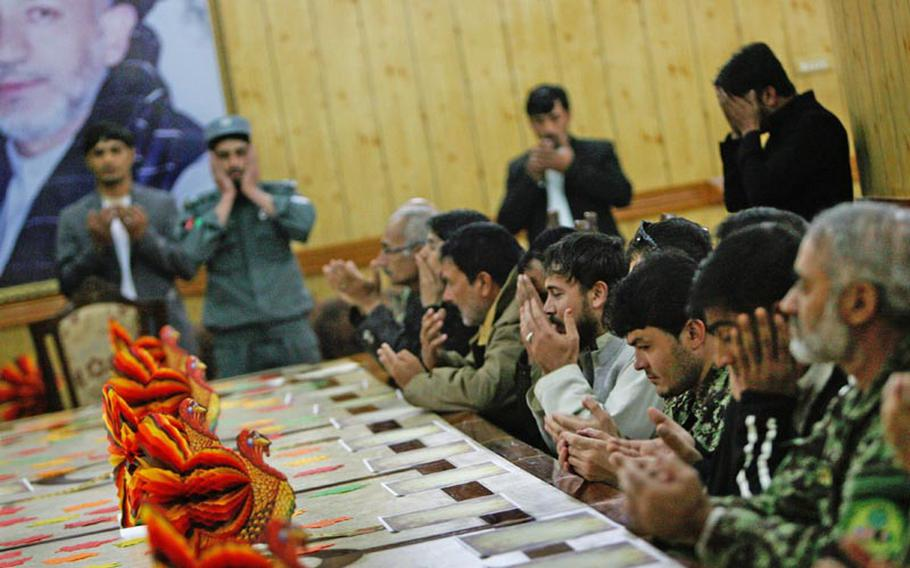 Afghan guests say a prayer before celebrating the first-ever Thanksgiving celebration at the Kandahar governor's provincial compound in Kandahar City, Afghanistan on November 22, 2012.