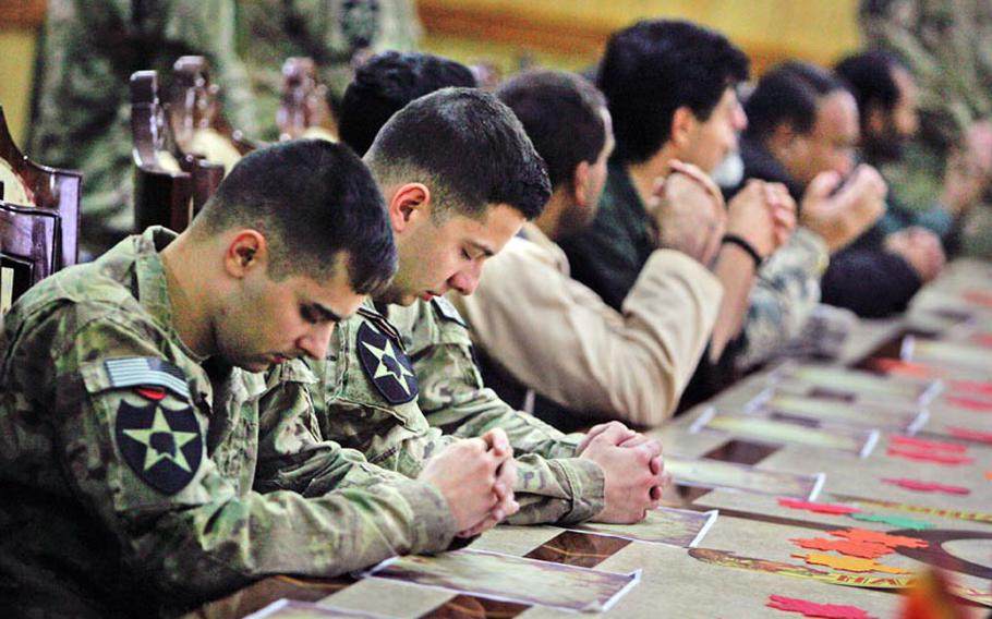 U.S. and Afghan guests pray before having Thanksgiving dinner at the Kandahar governor's provincial compound in Kandahar City, Afghanistan on November 22, 2012.