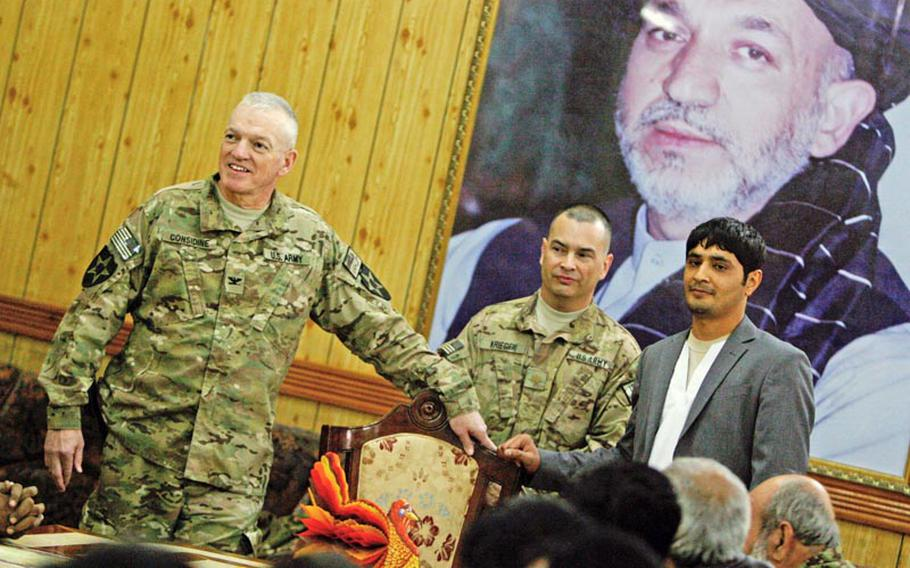 U.S. Col. Mike Considine, left, speaks to guests as Maj. Gerald Krieger and Afghan linguist Sameem listen during the first-ever Thanksgiving dinner celebration at the Kandahar governor's provincial compound in Kandahar City, Afghanistan on November 22, 2012.