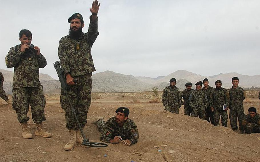 First Lt. Abdul Halim of the Afghan National Army makes a point while instructing fellow soldiers in the detection of buried explosive devices during a class at Camp Parsa in Khost province. The man on the ground is marking the perimeter of a suspected device, in this case a replica used on a training lane. A team of U.S. Army mentors pushed for creation of the course, which is being taught by Halim, an officer in the brigade's route clearance company.