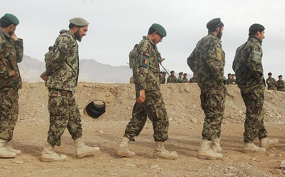 Soldiers from the Afghan National Army's 1st Brigade, 203rd Corps, file past a replica culvert as part of training on the detection and disabling of improvised explosive devices at Camp Parsa in Khost province. A team of U.S. Army mentors pushed for creation of the course, which is being taught by an Afghan soldier in the brigade's route clearance company.