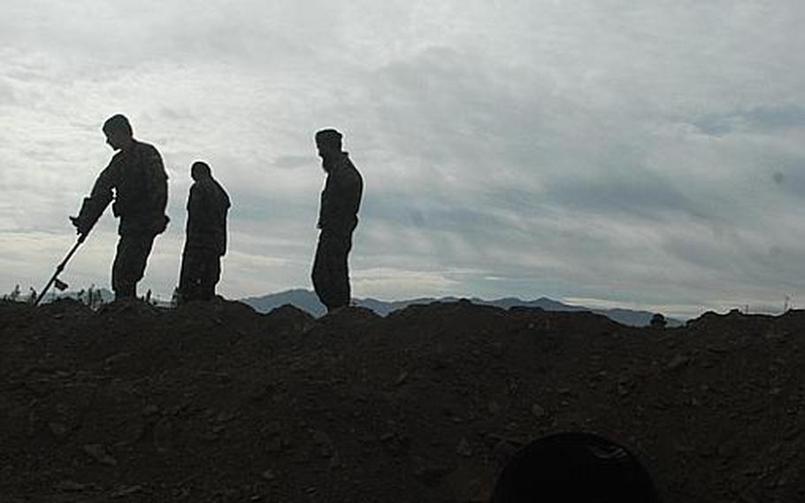 First Lt. Abdul Halim, right, of the Afghan National Army's 1st Brigade, 203rd Corps, guides soldiers during training on improvised explosive devices at Camp Parsa in Khost province. A team of U.S. Army mentors pushed for creation of the course, which is being taught by Halim, an officer in the brigade's route clearance company.