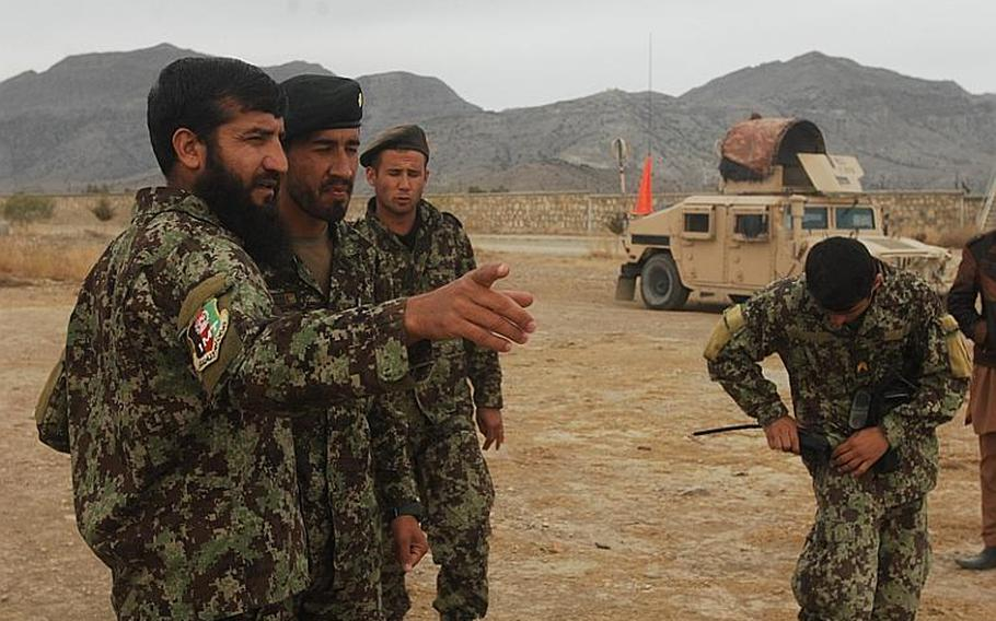 Afghan National Army 1st Lt. Abdul Halim, left, instructs a soldier during training on improvised explosive devices at Camp Parsa in Khost province, Afghanistan. The course is a first for the local ANA brigade, which wants to expand route clearance capabilities across its battalions.