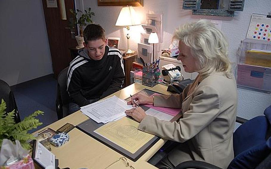 Patty Carden, a guidance counselor at Ramstein High School in Germany, and senior Josh Wallworth discuss his transcript and his hopes to attend either Auburn University or the U.S. Air Force Academy. Department of Defense schools in Europe and the Pacific have stepped up training on transcript management after a review revealed numerous errors in students' records.