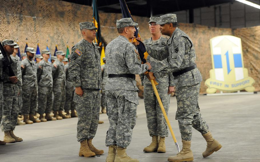 The incoming commander of the 7th Civil Support Command, Brig. Gen. Paul Benenati, center left, takes the unit's colors from Maj. Gen. Aundre Piggee, as outgoing commander Brig. Gen. Mark Hendrix watches at the 7th CSC's change-of-command ceremony at Rhine Ordnance Barracks in Kaiserslautern, Germany, Friday. To Benenati's left is Command Sgt. Maj. Michael Biere.