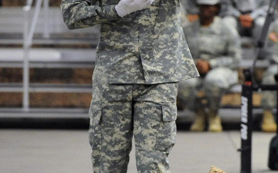 First Lt. Dustin Tutin, of the 529th Military Police Company Honor Guard Battery, carries a ceremonial shell casing that he presented to Brig. Gen. Mark Hendrix, the outgoing commander of 7th Civil Support Command.  Brig. Gen. Paul Benenati took over the reins of the 7th CSC from Hendrix at a change-of-command ceremony Friday at Rhine Ordnance Barracks in Kaiserslautern, Germany.