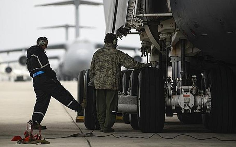 Air Force Staff Sgt. Brian Parker, left, a crew chief with the 721st Air Mobility Group, and Tech. Sgt. Greg LeVengie, a loadmaster with the 337th Airlift Squadron, inspect a C-5 Galaxy at Ramstein Air Base, Germany, on Tuesday, Jan. 8, 2013.