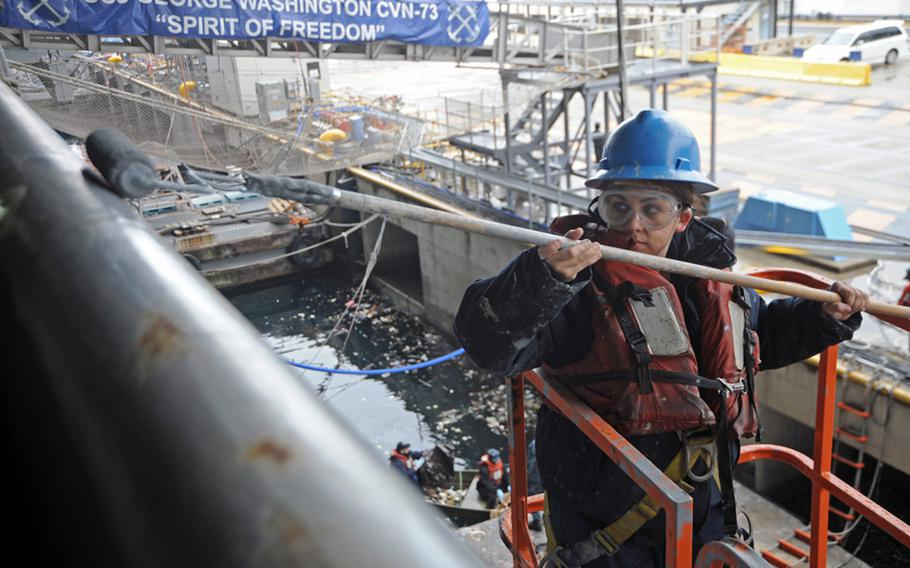 Seaman Casey Perrow paints the side of the aircraft carrier USS George Washington in December. The ship and its strike group could be the only crisis-ready carrier group in the Navy by October if automatic spending cuts set to be triggered in March aren't canceled, according to Navy documents. The Yokosuka, Japan-based carrier is scheduled for a six-month maintenance period, beginning in about a week.