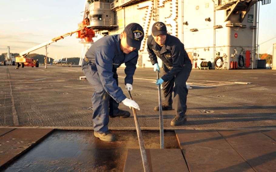 Seamen David Cauichcumi and Geoffrey Worcester remove impact pads from the flight deck of the aircraft carrier USS George Washington in November. The ship and its strike group could be the only crisis-ready carrier group in the Navy by October if automatic spending cuts set to be triggered in March aren't canceled, according to Navy documents. The Yokosuka, Japan-based carrier is scheduled for a six-month maintenance period, beginning in about one week.
