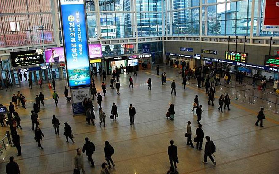 Passengers walk through Seoul Station on Tuesday evening, shortly after North Korea announced that foreigners should leave the country for their safety in case of war. Many in South Korea, accustomed to hearing threats from the North, have shown little serious concern about a possible military confrontation with Pyongyang.