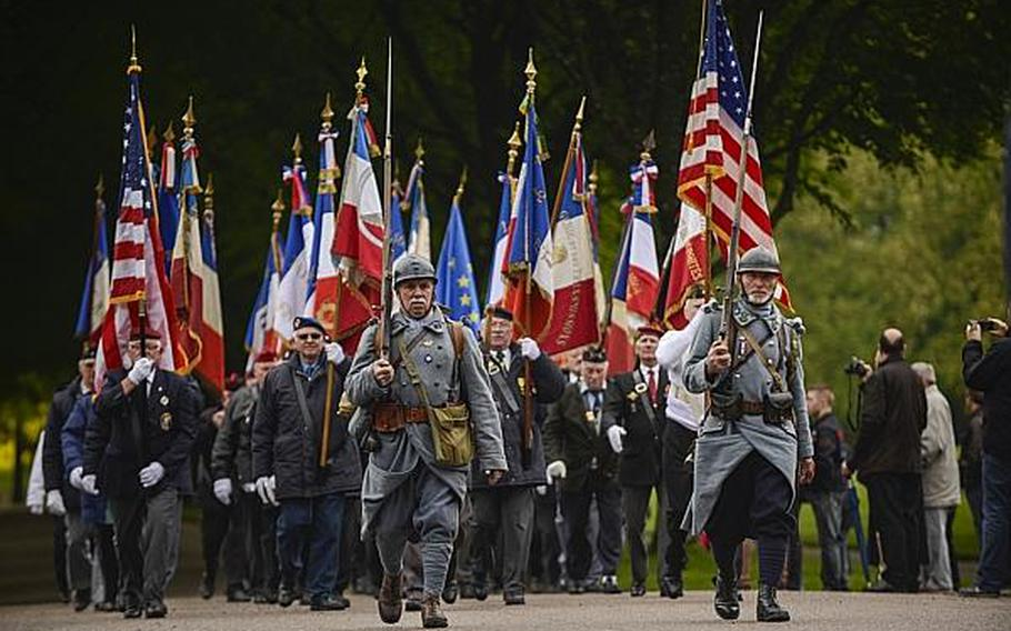 French veterans carry flags during a pass and review Sunday morning after an American Memorial Day ceremony at the Meuse-Argonne American Cemetery and Memorial in France.  Joshua L. DeMotts/Stars and Stripes