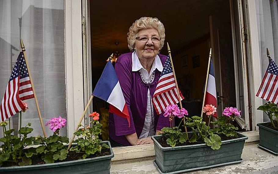 A woman from the village of Romagne-sous-Montfaucon watches the French Band of the Armored Cavalry perform in front of her house after an American Memorial Day ceremony at the nearby Meuse-Argonne Cemetery and Memorial in France.  Joshua L. DeMotts/Stars and Stripes