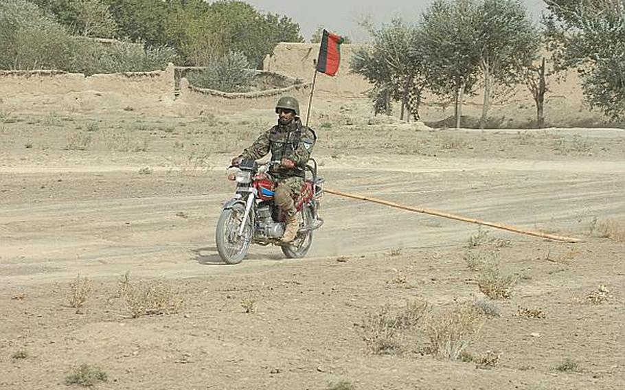 An Afghan soldier drags a rake behind a motorcycle to search for roadside bombs in Zabul Province in 2010.