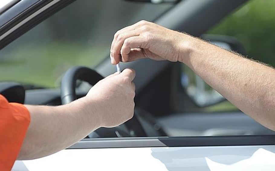 A motorist takes a card from a  member of the Better Opportunities for Single Soldiers program on Tuesday, July 2, 2013, at Clay Kaserne in Wiesbaden, Germany. Troops with the program, along with military police and other garrison members, handed out cards that discourage drinking and driving ahead of the long holiday weekend.