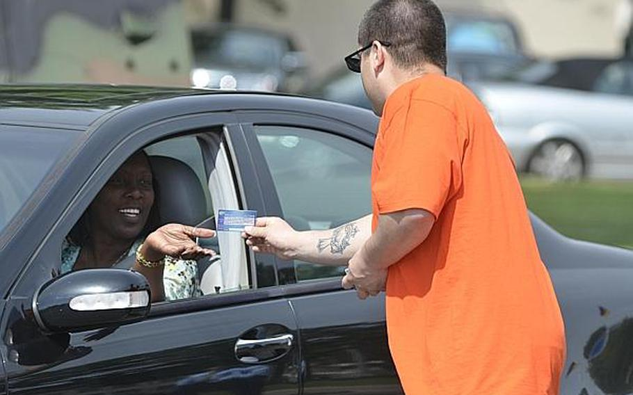 A motorist takes a card from Spc. Theodore Lozano, a member of Wiesbaden, Germany's Better Opportunities for Single Soldiers program, at Clay Kaserne on Tuesday, July 2, 2013. The cards offered information aimed to discourage drinking and driving ahead of the long holiday weekend.