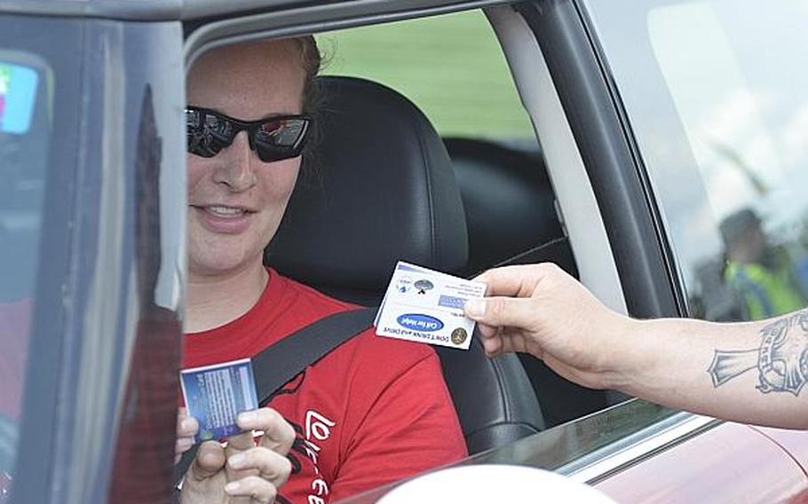 A Wiesbaden military community member speaks with a member of Better Opportunities for Single Soldiers after receiving an information and designated driver card on Tuesday, July 2, 2013, at Clay Kaserne.   Mark Patton/Stars and Stripes