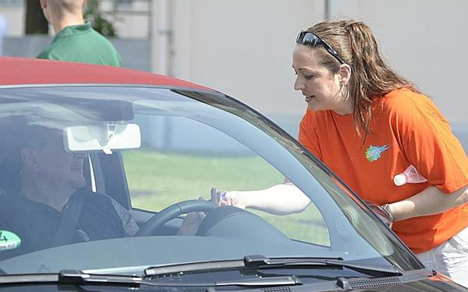 Sgt. Susan Noga with the U.S. Army Europe headquarters hands out informational and designated driver cards to motorists exiting Wiesbaden's Clay Kaserne on Tuesday, July 2, 2013.