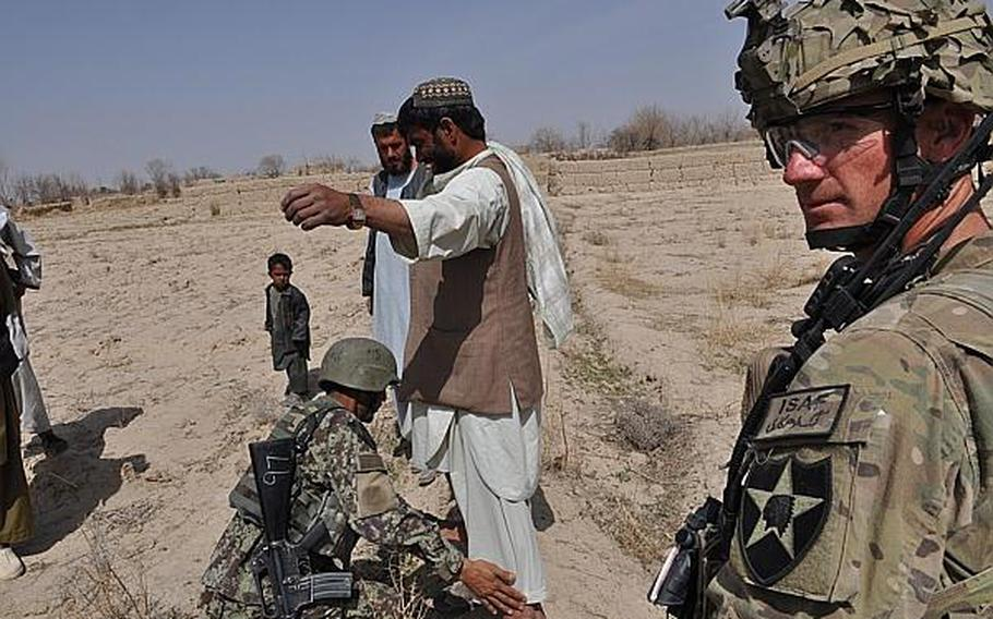 An Afghan soldier searches a villager in in Kandahar province while a U.S. soldier looks on.  Recently, some Afghans who have attacked coalition troops have managed to escape prosecution, perhaps with the help of others sympathetic to the Taliban cause.