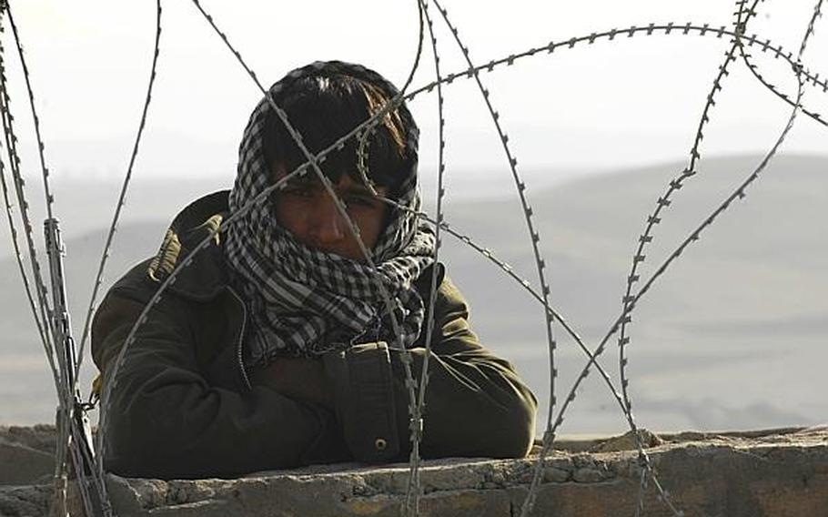 An Afghan guard peers out from behind the walls of a prison in Qalat, Afghanistan, in this 2009 photo. Recently, some Afghans who have attacked coalition troops have managed to escape prosecution, perhaps with the help of others sympathetic to the Taliban cause.