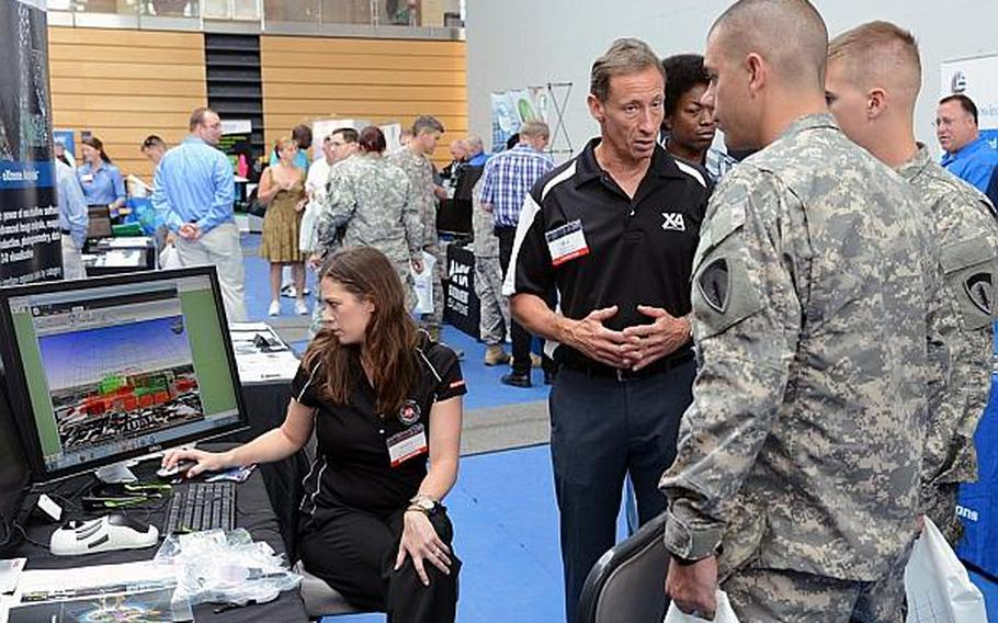 As Jessica Durst demonstrates, Rick Racine of BAE Systems explains to Spc. Jerry Akins and Sgt. Ken Pehoski how the company's GXP Xplorer works at the technology expo at Clay Kaserne in Wiesbaden, Germany, Friday, July 26, 2013. More than 50 exhibitors showed their goods at the expo, which focused mostly on communications and security. The GPX Xplorer is a management application for geospatial data.