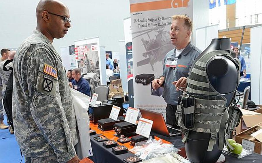 Staff Sgt. Michael Watson of U.S. Army Europe's Operations Company listens as AR Modular RF's Mike Katzer describes the company's boosters for tactical radios  at the technology expo at Clay Kaserne in Wiesbaden, Germany, Friday, July 26, 2013. More than 50 exhibitors showed their goods at the expo.