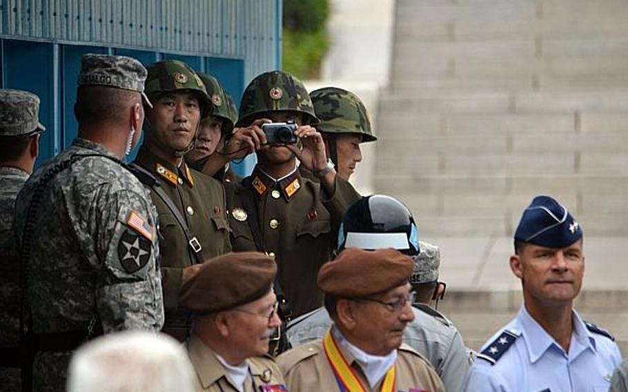 A North Korean soldier takes photos of the 21-nation delegation gathered at the demarcation line between North and South Korea at the Joint Security Area, South Korea, July 27, 2013.