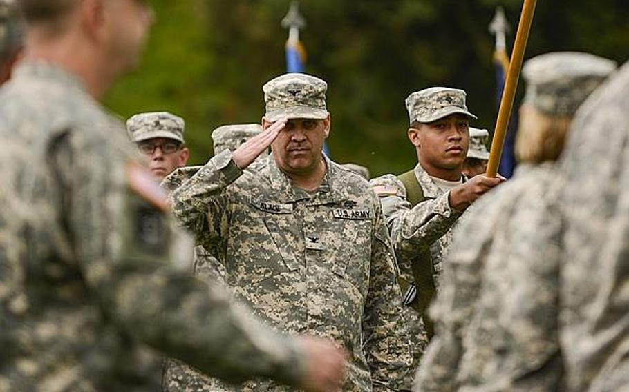 U.S. Army Col. Thomas Slade salutes the official party as they inspect the troops during a command relinquishment ceremony at the Europe Regional Medical Command Tuesday, July 30, 2013, at Sembach Kaserne, Germany.