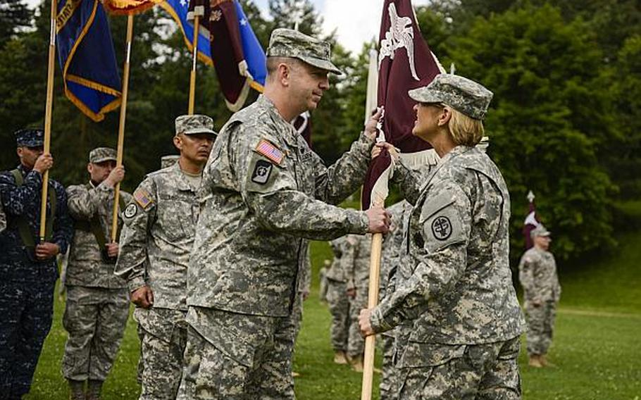 U.S. Army Col. John P. Collins, left, takes the guidon from Lt. Gen. Patricia D. Horoho, the Army Surgeon General, as he assumes temporary commnad of the Europe Regional Medical Command on Tuesday, July 30, 2013, at Sembach Kaserne, Germany.