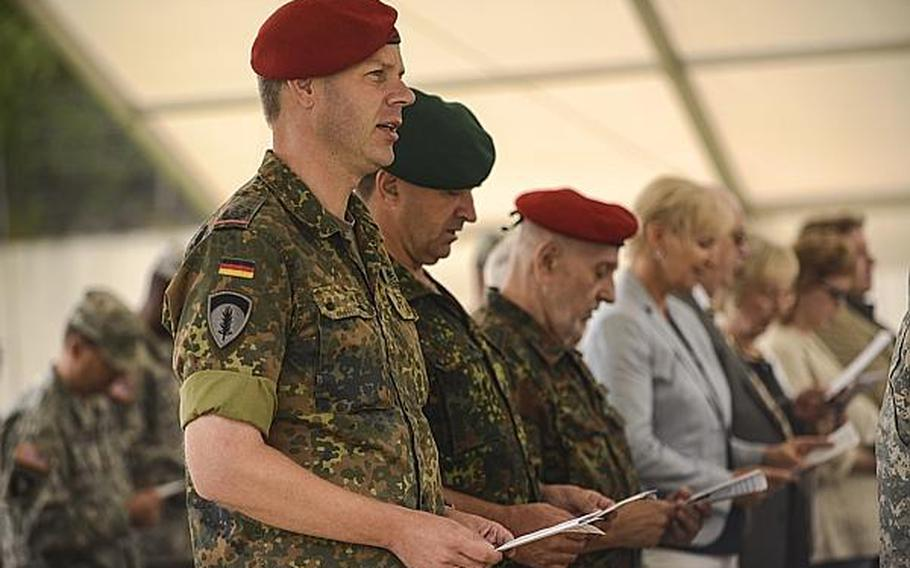 Attendees at a Europe Regional Medical Command relinquishment of commnad ceremony at Sembach Kaserne, Germany, sing the Armed Forces Medley at the conclusion of the ceremony Tuesday, July 30, 2013.