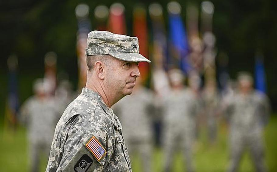 U.S. Army Col. John P. Collins, interim commander, Europe Regional Medical Command, looks toward the crowd at the end of the ceremony in which he took charge on Tuesday, July 30, 2013, at Sembach Kaserne, Germany.
