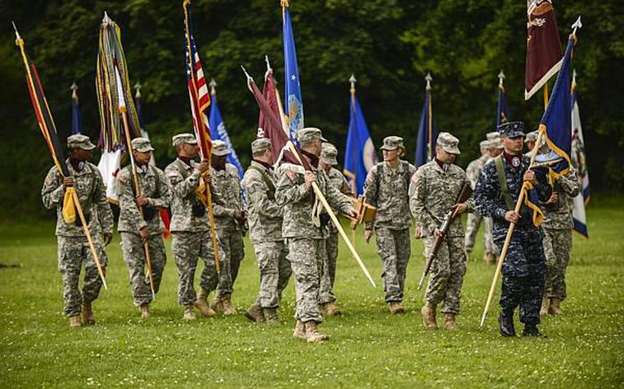 The multi-service color guard walks off the parade field at the end of a relinquishment of command ceremony for the Army's top medical post in Europe on Tuesday, July 30, 2013, at Sembach Kaserne, Germany.