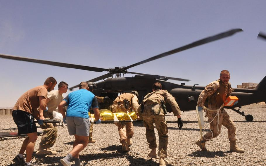 U.S. and Czech medics rush a young Afghan boy to a black hawk for a medevac after he was shot in the back of the head by a ricochet bullet on a firing range at COP Soltan Kheyl. The boy was said to have been collecting empty bullet cases when he was hit.
