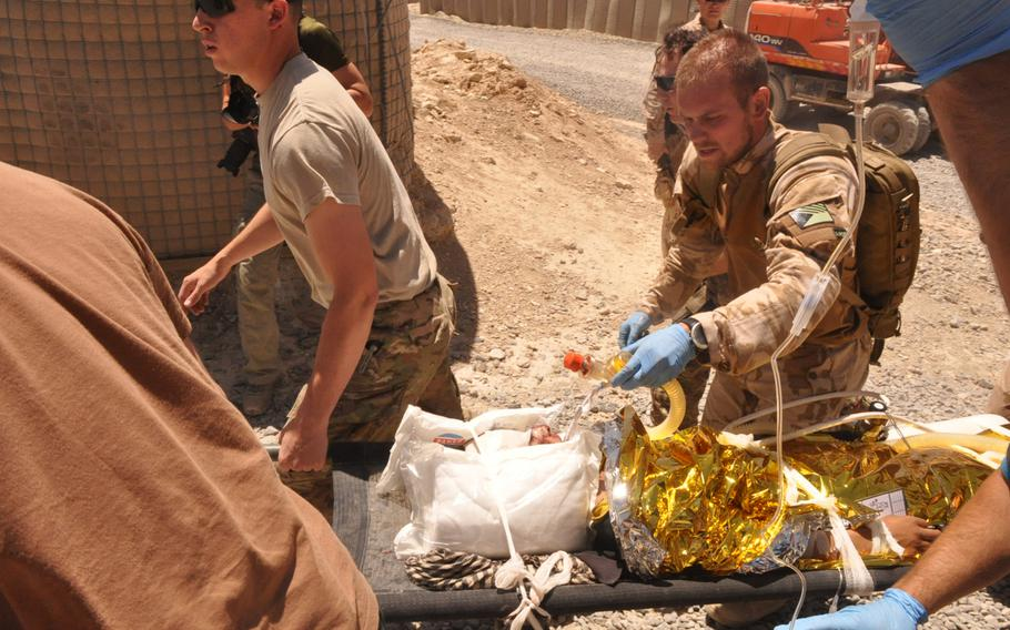 U.S. and Czech medics rush a young Afghan boy to a black hawk helicopter for a medevac after he was hit in the back of the head by a stray bullet on a firing range at Combat Outpost Soltan Kheyl. He was said to have been collecting empty bullet cases, which is common for both children and adults so they can sell the brass.