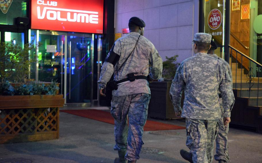 Members of the Osan Air Base joint town patrol walk toward a local bar to check on sevicemembers at the Songtan Entertainment District in South Korea, Aug. 17, 2013.