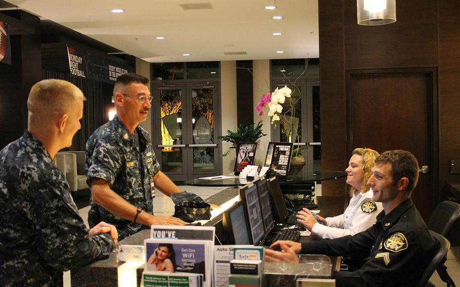 """Petty Officer 1st Class Charles Dowding (far left) and Chief Petty Officer David Auxier talk to James Niessner, a security guard with Off Duty Officers and Robin Wilkie, a concierge, at the front desk of an apartment-style living facility for enlisted sailors at Naval Base San Diego. Dowding and Auxier were conducting a patrol of the base as part of an effort to maintain """"good order and discipline"""" and prevent sexual assaults."""