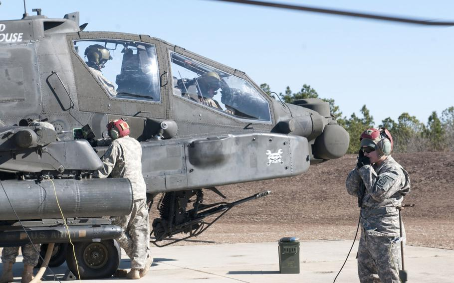 Army Spc. Morgan Mayes, an armament specialist with the 1st Attack Reconnaissance Battalion, 82nd Combat Aviation Brigade, communicates with pilots as her team prepares to load ammunition onto AH-64 Apache Longbow helicopters during an aerial gunnery range held at Fort Bragg, N.C., on Feb. 18, 2013.