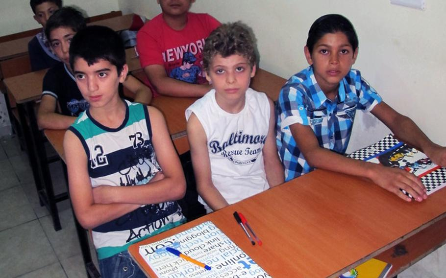 An English class for 12-year-old Syrian refugee children at the Human Essence First School in Antakya, Turkey, on the first day of class, Monday, Sept. 16, 2013.
